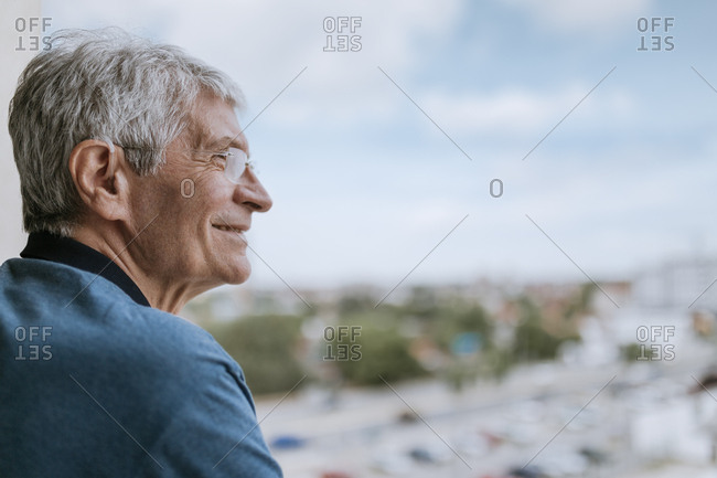 Smiling senior man with hearing aid outdoors
