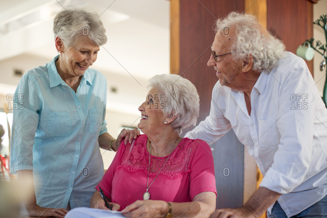 Senior woman signing a contract- friends reassuring her