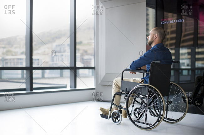 Man in wheelchair looking out of window in office