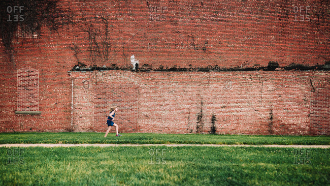 Girl running in front of a brick wall