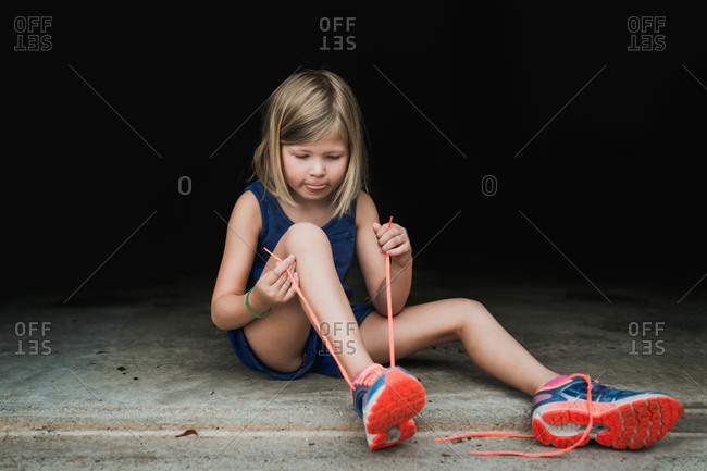 Little girl learning to tie shoe laces