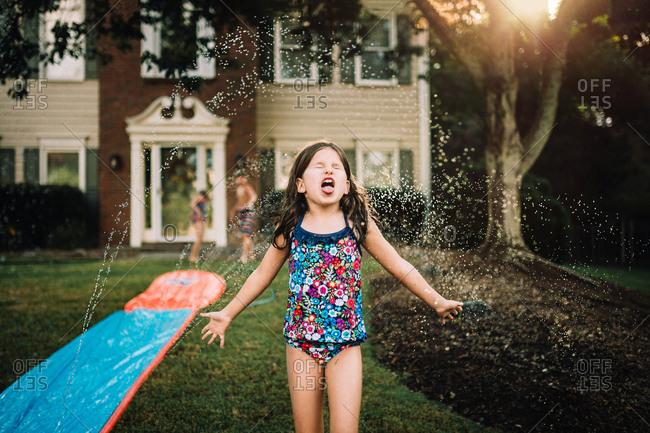 Little girl playing in a sprinkler with siblings in background