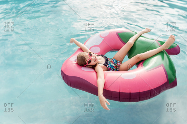 Little girl relaxing a strawberry floaty in the pool