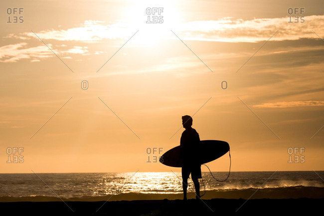 Surfer carrying board on the beach at sunset