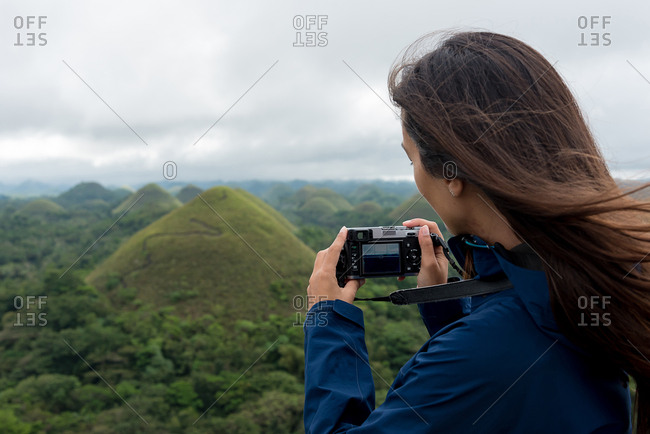 Woman outdoors taking pictures with a camera in her hands in Chocolate Hills. Bohol, Philippines