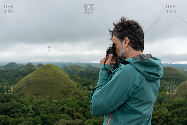Man outdoors taking pictures with a camera in her hands in Chocolate Hills. Bohol, Philippines