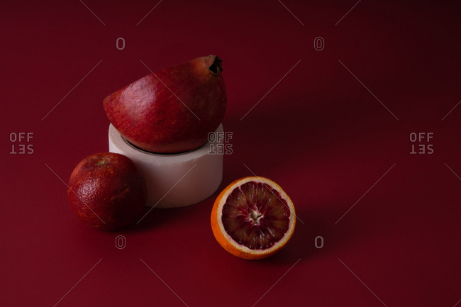 Still life with pomegranate and red orange on red background