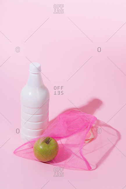 Still life with plastic milk bottle on pink background