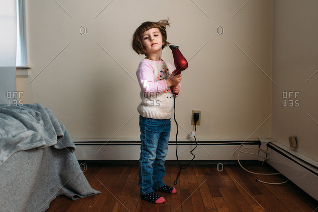 Little girl drying her hair with a blowdryer.