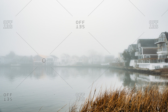 Houses on a pond on a foggy day in New England.