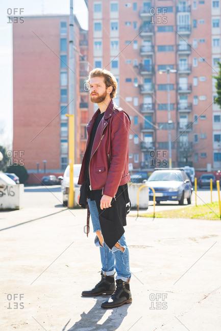 Young beautiful bearded man posing outdoor looking away