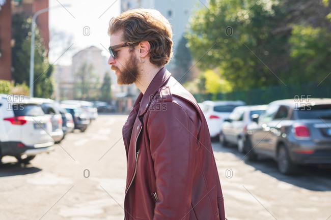 Young beautiful bearded man walking outdoor looking away