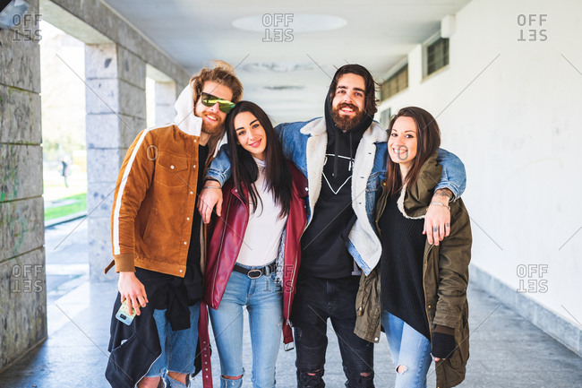 Four people both male and female posing looking camera hugging