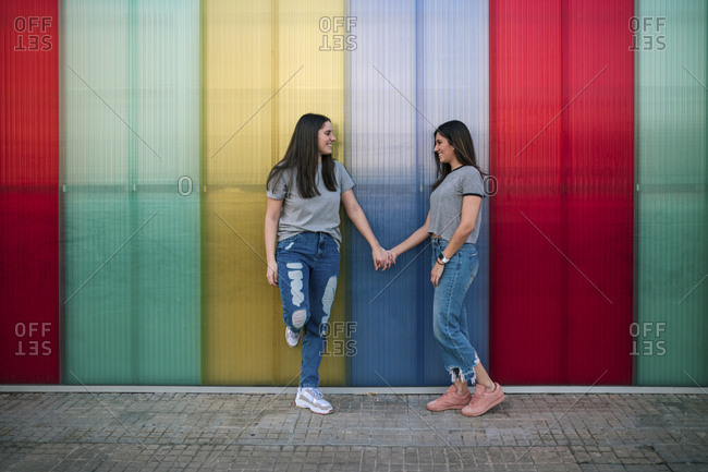 Lesbian couple looking each other with a colorful background