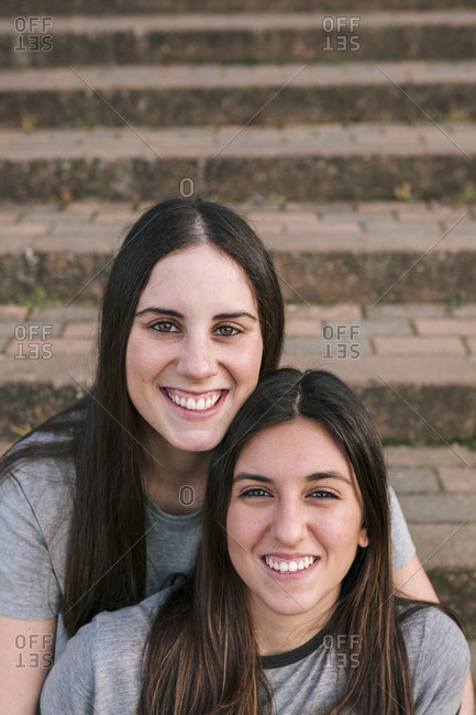 Young couple of lesbians smiling sitting on the stairs of a park