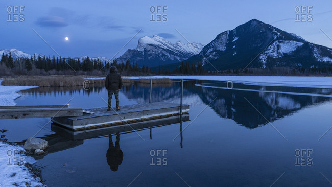 Woman on tranquil winter lake dock, looking at full moon above mountains, Banff, Alberta, Canada