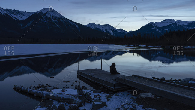 Woman sitting on tranquil winter lake dock with mountain view at night, Banff, Alberta, Canada