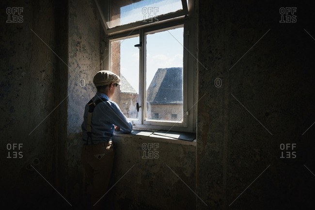 Boy looking out sunny window