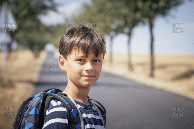 Portrait confident schoolboy with backpack on sunny road