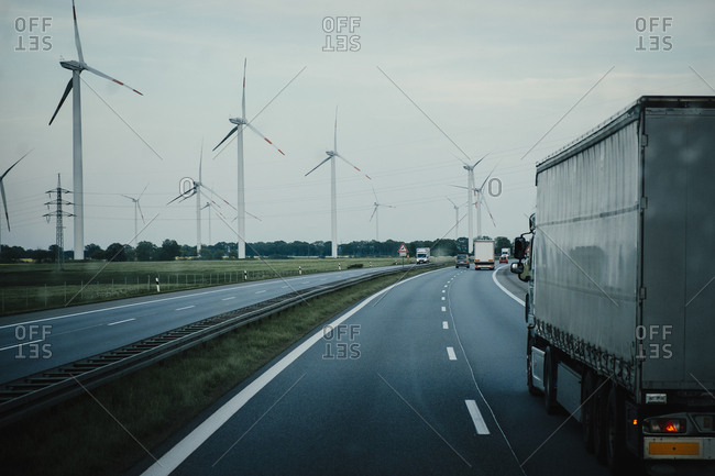 Trucks and cars moving on highway along wind turbines, Brandenburg, Germany