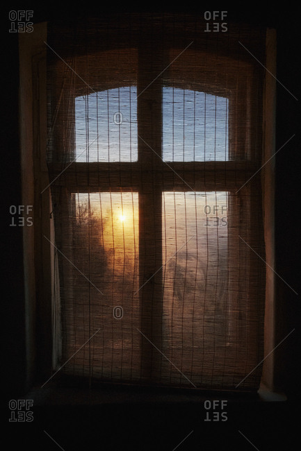 Ethereal sunrise behind gauze window curtain