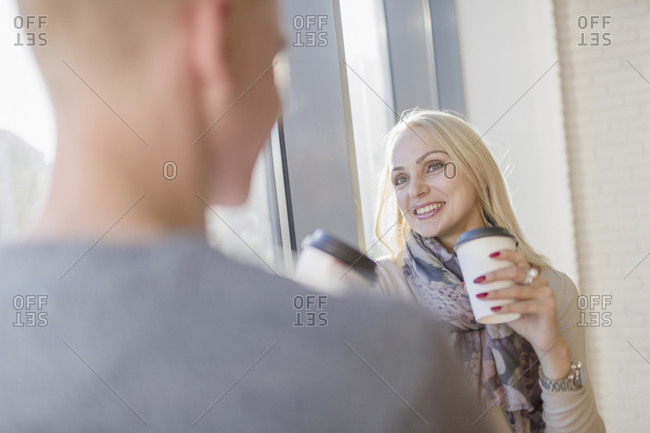 Smiling businesswoman drinking coffee with colleague in cafe