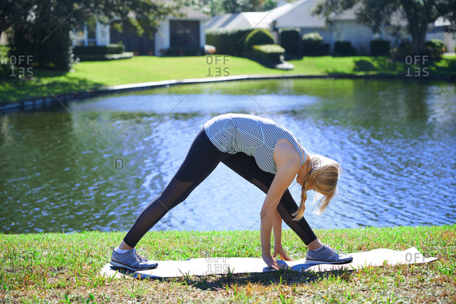Woman at the backyard with lake doing stretching exercise