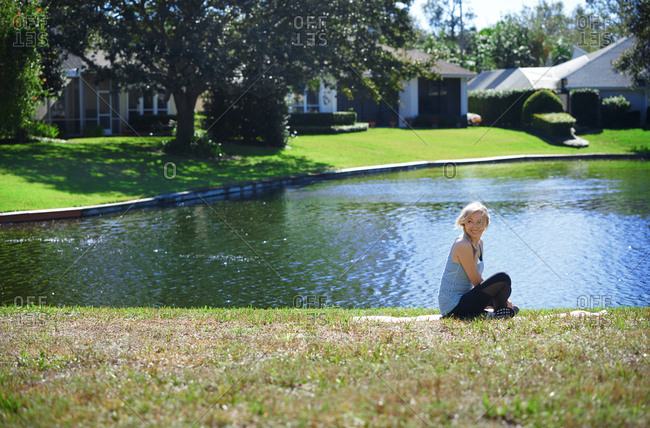 Woman at the backyard with lake relaxing after exercising