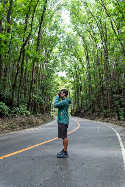 Man with a photography camera on a road surrounded by densely planted mahogany trees in Man Made Forest. Bohol, Philippines