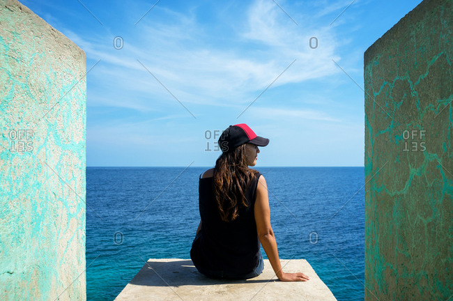 Back view of a woman sitting on the edge of a trampoline above the ocean in Siquijor, Philippines