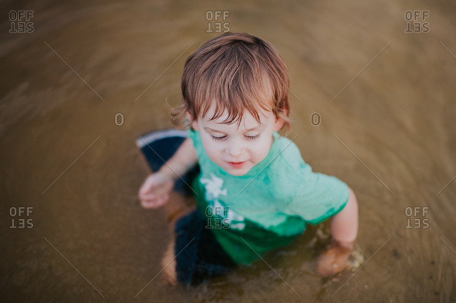 Little boy sitting in water