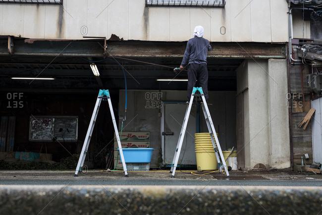 Tahara, Japan - September 14, 2018: Man on ladder working on building