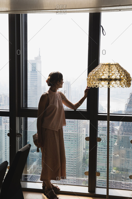 Beautiful woman looking out high-rise hotel window