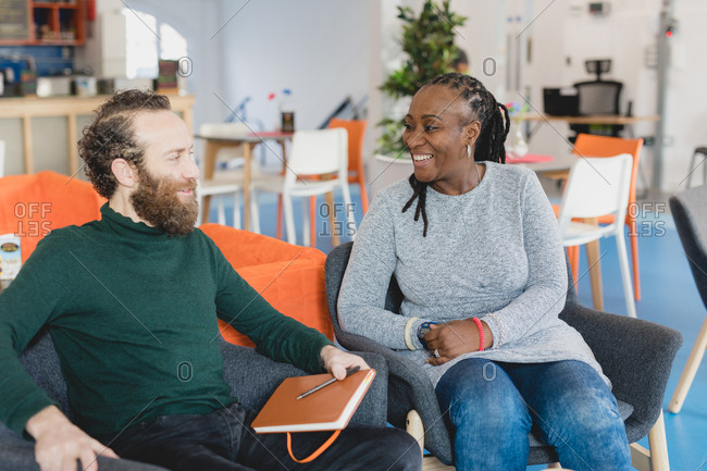 Man and woman laughing during business meeting