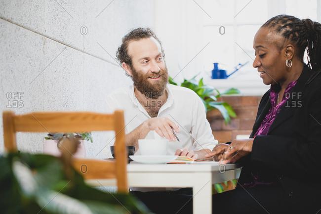 Man and woman going over notes during business meeting