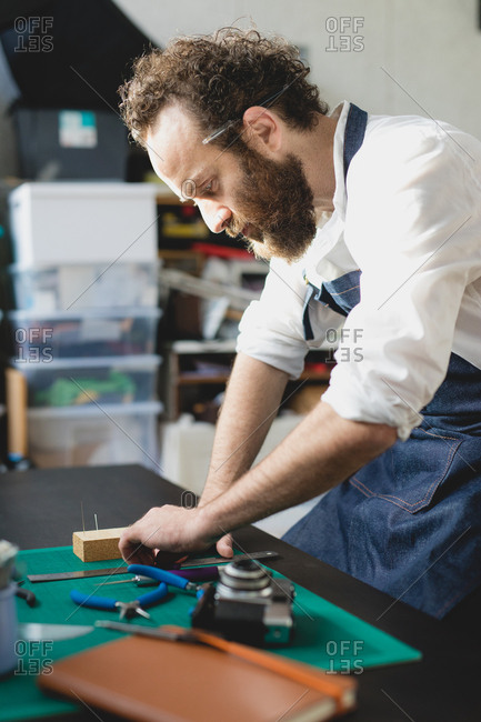 Man using tools while woodworking in a studio