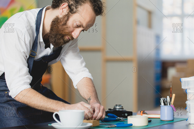 Man with beard doing woodworking in a studio