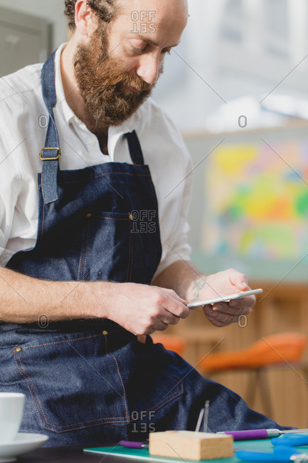 Man with beard using cell phone while woodworking in a studio