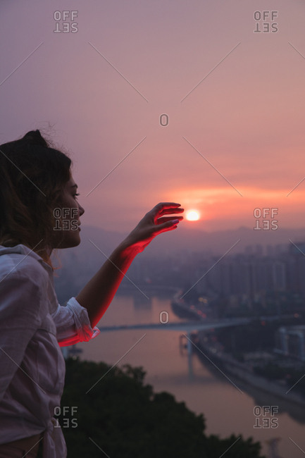 Woman reaching towards the sunset
