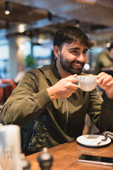 Man sitting in cafe drinking a latte