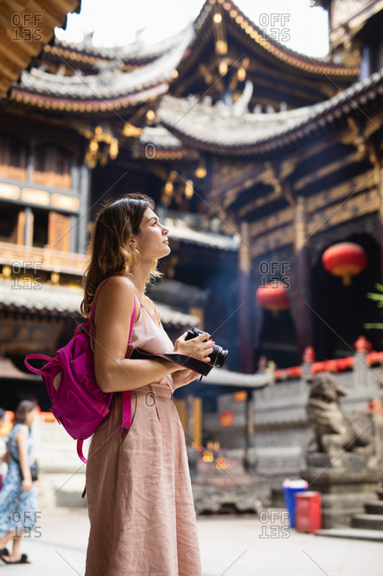 Woman with camera looking at a temple in China