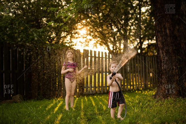 Two kids playing with hose in the summertime
