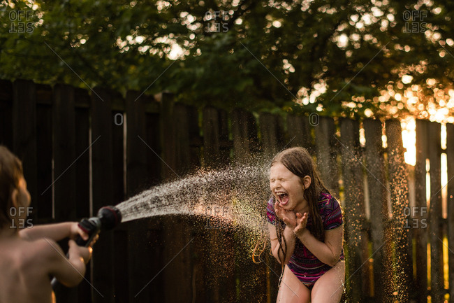 Little boy spraying sister with garden hose