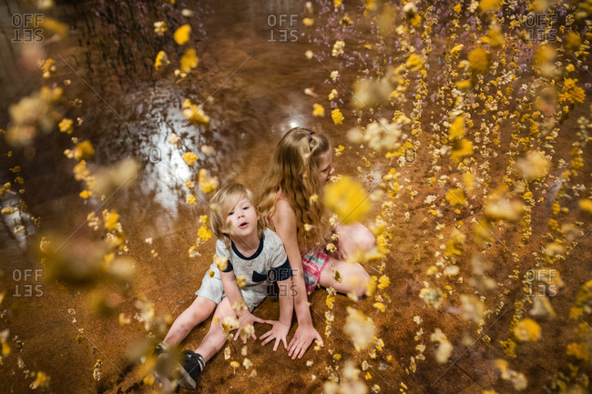 Two kids surrounded by flower garland
