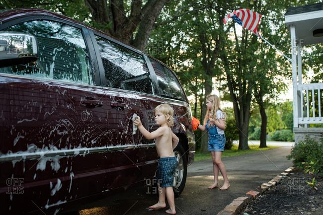 Siblings helping wash a minivan