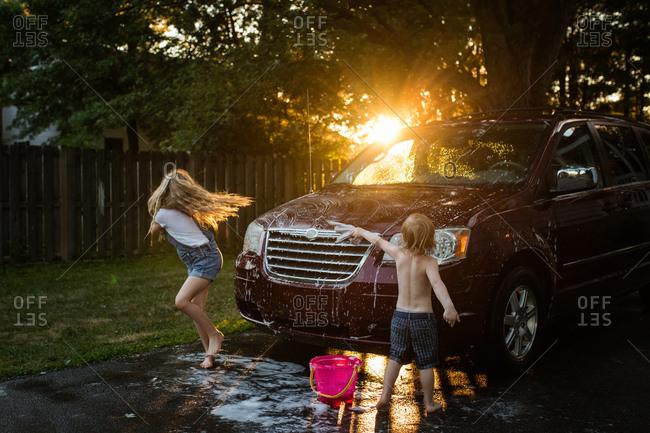 Two kids washing a minivan at sunset
