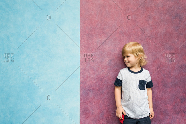 Portrait of a little blonde boy standing in front of red and blue wall