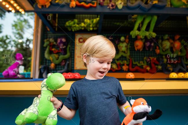 Little boy holding stuffed animals won at a fair