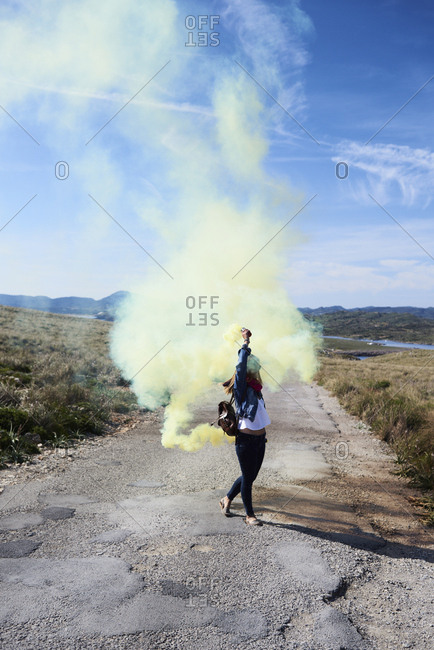 Girl walking on road with yellow smoke bomb in countryside