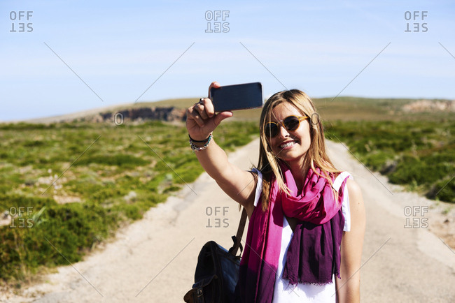 Cheerful woman in sunglasses and purple scarf taking selfie in sunny countryside